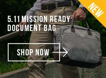 Man walking down the stairs wearing white shirt and sand coloured trousers holding a grey 5.11 mission ready document bag