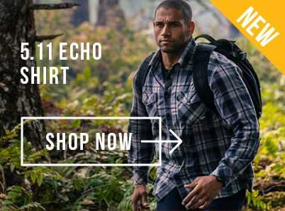 Man walking through the woods wearing a blue 5.11 echo long sleeve shirt carrying a black backpack