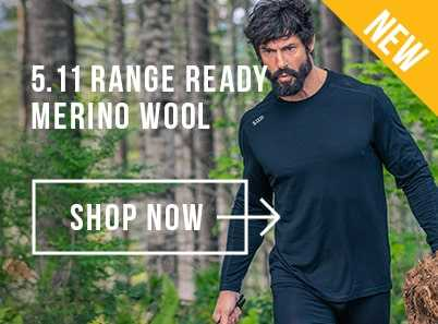 Man with dark beard walking through the woods wearing a black 5.11 long sleeved merino wool top and black trousers.
